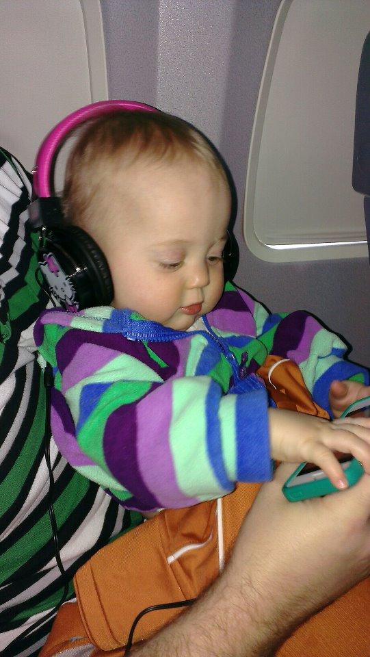 Isla with headphones on plane